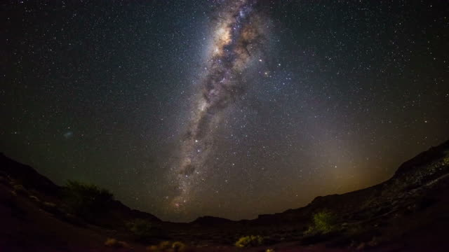 the apparent rotation of an outstandingly bright milky way and starry sky beyond mountain of the namib desert, namibia. time lapse video. - fish eye video stock e b–roll