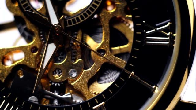 vidéos et rushes de les flèches sur la montre en or - rouage mécanisme