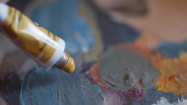 The Art of painting. An active senior woman with her hobbies. Handmade painting, working space, handcraft, artwork, ideas, close up