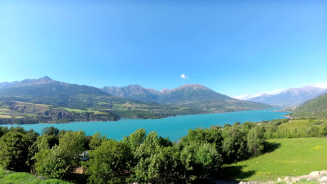 the artificial lake serre-poncon in the french alps. the lake water is used for irrigation of agricultural fields. - barrage de serre poncon stock videos & royalty-free footage