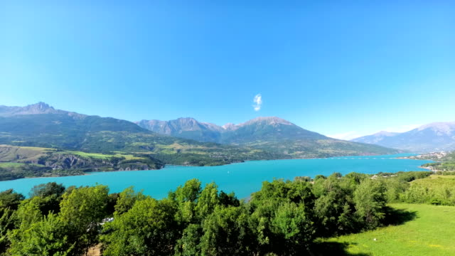 the artificial lake serre-poncon in the french alps. the lake water is used for irrigation of agricultural fields - barrage de serre poncon stock videos & royalty-free footage
