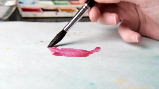 The artist at work draws watercolors. Close up.