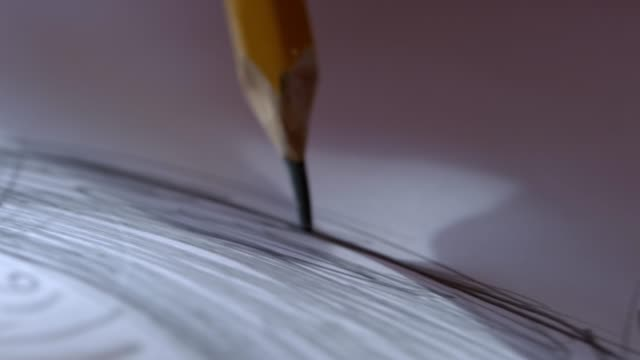 The artist drawing a flat line with a black pencil. Artists hands drawing wooden pencil writes line on paper.