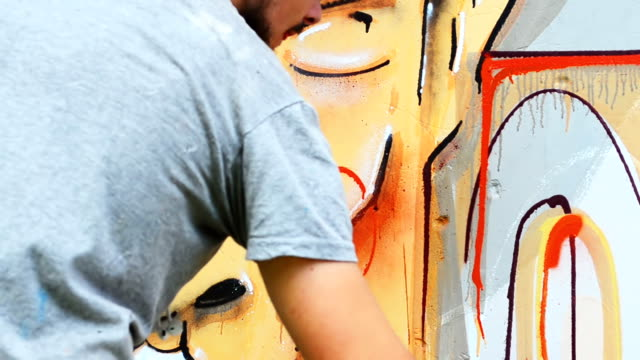 The artist draws graffiti on a fence.Abstract drawing. video