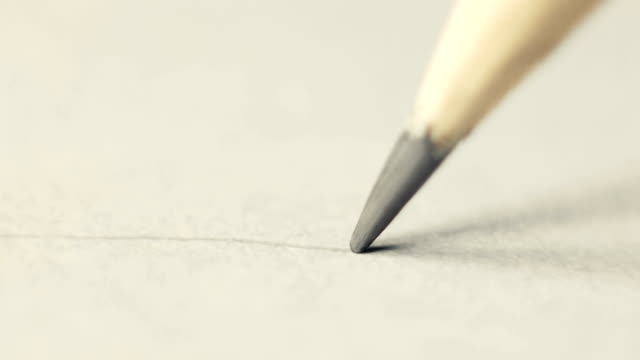The artist draws with a pencil on paper. Or just a letter on paper