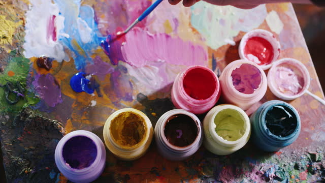 The artist mixes paint. Poppy brush in the paint, and selects the desired shade video