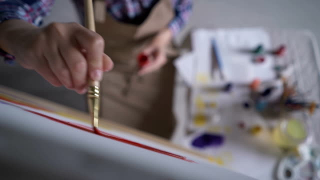 the artist paints on canvas and smears a brush. canvas stands on the easel. the artist draws at the easel. - eastern european descent stock videos & royalty-free footage