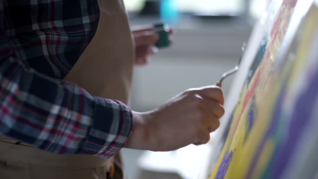 the artist paints on canvas and smears a palette knife. canvas stands on the easel. the artist draws at the easel. - eastern european descent stock videos & royalty-free footage