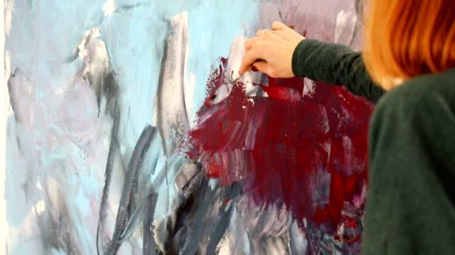 the artist paints with acrylic red and dark colors. drawing with spatula and acrylic paints. - szpatułka przybór do gotowania filmów i materiałów b-roll
