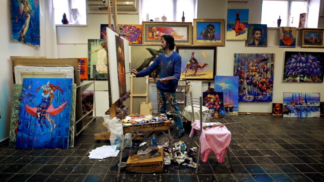 The artist paints with oil painting. In the studio, among his own works video