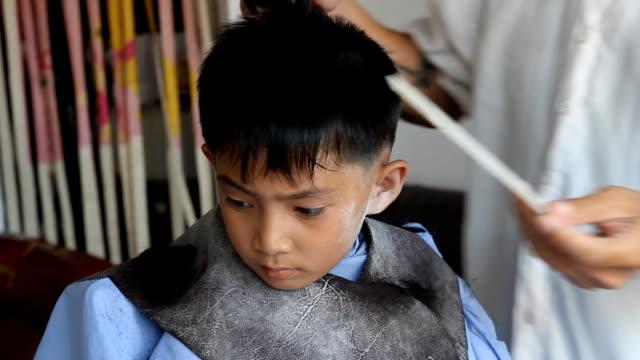 The Asian boy having a haircut. video