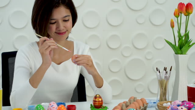 the asian young woman painting the colorful Easter egg