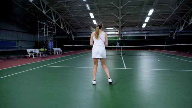 The athlete in white form throws the ball across the net during a tennis competition on the indoor court, the woman is actively moving with a racket video