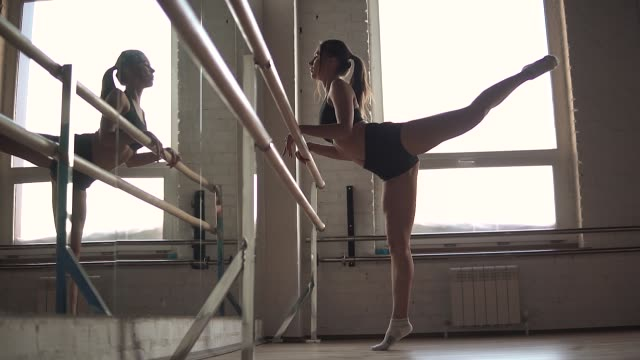 The athlete kneads before training in the gym. girl in sports clothes in front of a mirror The athlete kneads before training in the gym. girl in sports clothes in front of a mirror. doing the splits stock videos & royalty-free footage