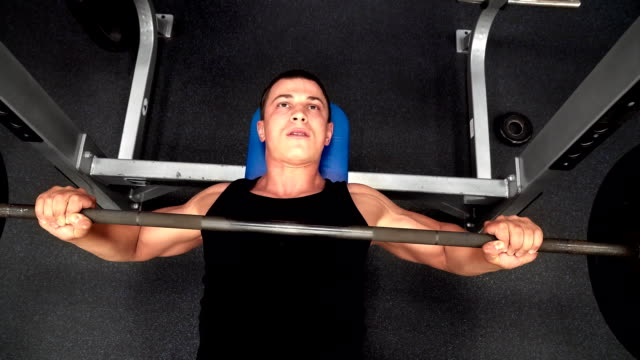 The athlete lifts a heavy barbell in gym video