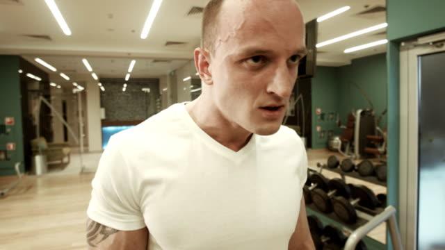 l'atleta i bodybuilder ascensori un bar in palestra - maglietta bianca video stock e b–roll