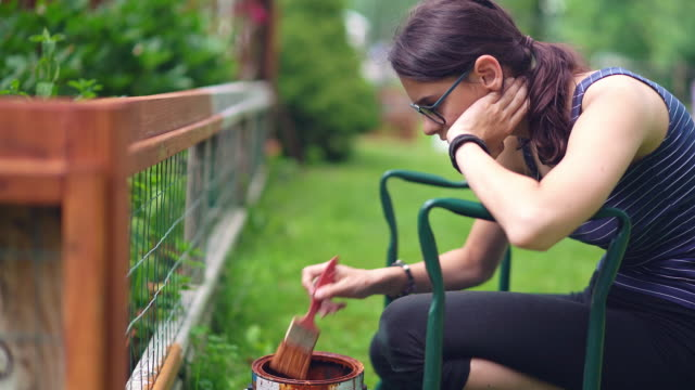 vídeos de stock e filmes b-roll de the attractive 15-years-old teenager girl painting the fence at the backyard - cercado