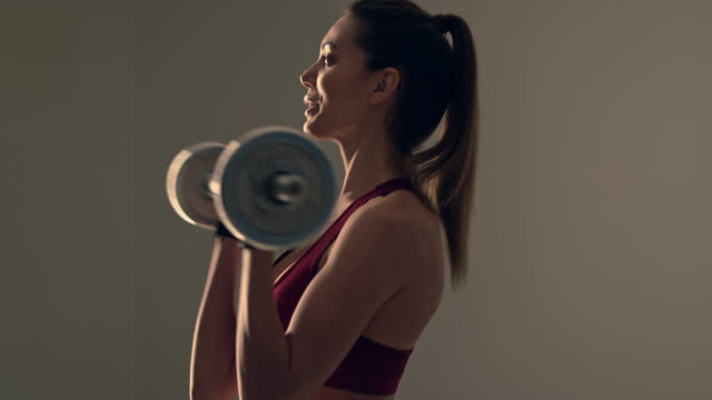 The attractive woman flexing muscles with barbell