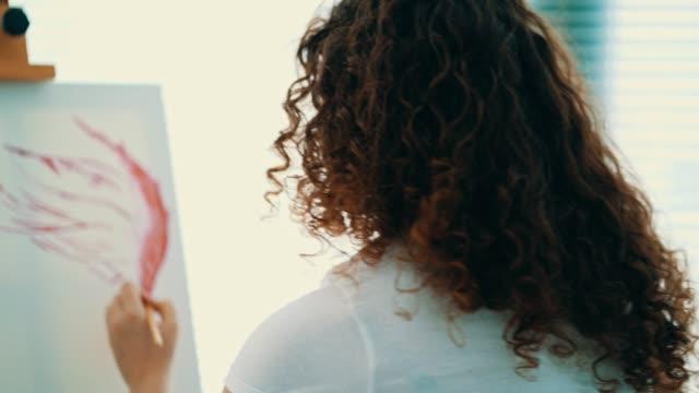 vidéos et rushes de la femme attirante peignant une image sur le chevalet - toile à peindre