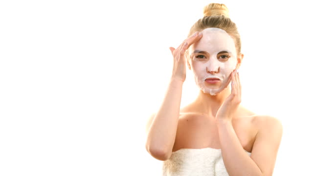 The attractive woman with a clean mask touching the face on the white background