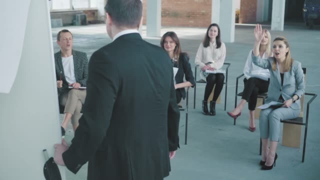 The audience asks questions to the young manager in a suit at the presentation. Creative office interior. Co-working life. Office workers video