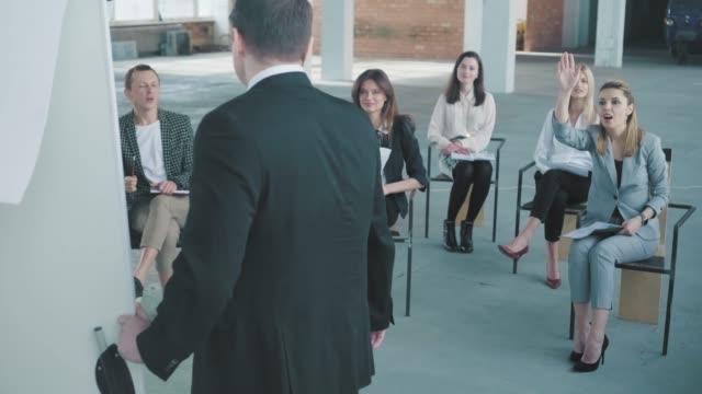 聴衆は、プレゼンテーションでスーツを着た若いマネージャーに質問します。クリエイティブなオフィスインテリア。コワーキングライフ。オフィスワーカー ビデオ