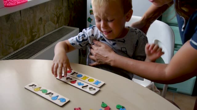 the autistic boy is naughty and does not want to engage an autistic child is naughty and hardly fulfills the tasks of an assistant - collects puzzles in forms autism stock videos & royalty-free footage