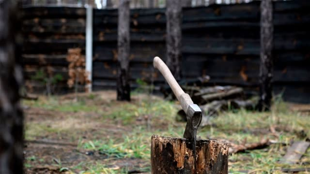 The axe for chopping firewood. The axe sticks out in the stump. firewood stock videos & royalty-free footage