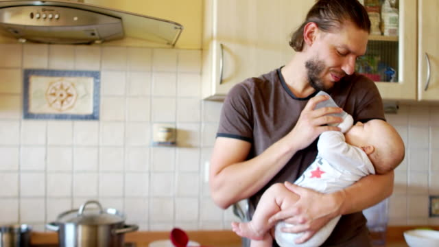 The baby eagerly drinks milk from the nipple in the hands of his father. The baby sneezes, the man smiles. Father's day, father's care video