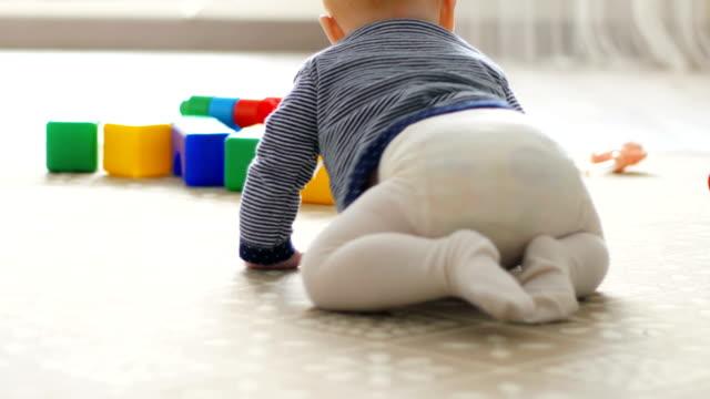 vidéos et rushes de la petite fille apprend à ramper, les premières tentatives de ramper. bébé rampe à la caméra, souriant et riant sur le sol dans la salle blanche. - ramper