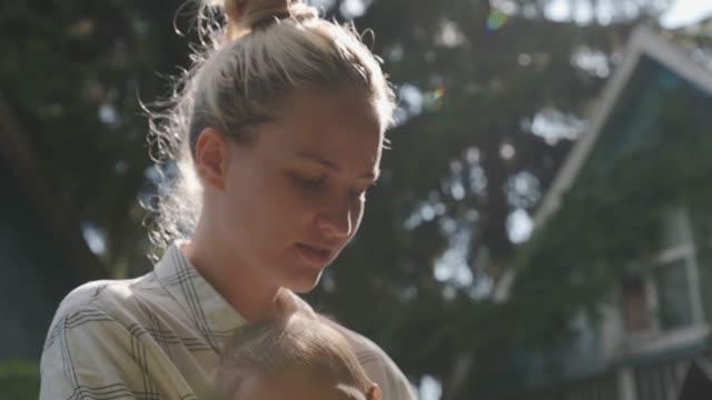 vidéos et rushes de le bébé dans les bras de la jeune fille regarde dans le cadre et sourit. - 0 11 mois