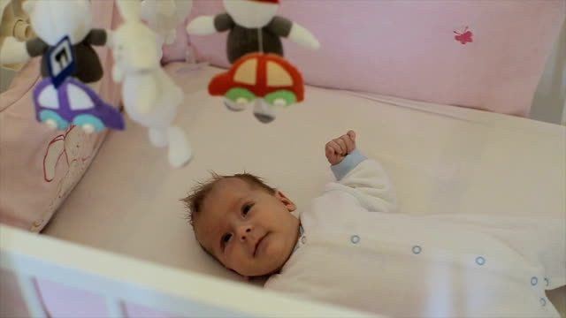 The baby is in the crib and watching over her toys video