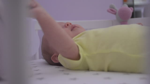 The baby lies in bed and looks at the toys video