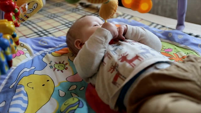 The baby lies on a bed and having fun with their toys video