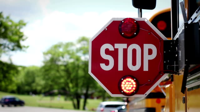 The back of school bus stop sign lights flashing and blinking near playground video