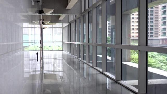 背景はコリドーと透明な窓です。公共の場所エリアの近代的な建物内の場所。 - 廊下点の映像素材/bロール