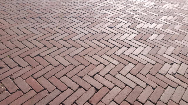 The background of the famous Red pavers Holland. A method of laying paving slabs with a diamond. Park path made of stone.