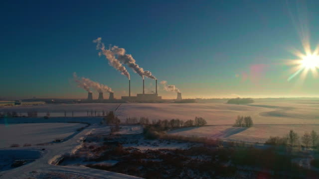 the bad ecology. the thermal power plant near by big city in the cold winter's day. aerial drone video with panoramic camera motion. - centrale termoelettrica video stock e b–roll