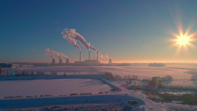 the bad ecology. the thermal power plant near by big city in the cold winter's day. aerial drone video with static camera. - centrale termoelettrica video stock e b–roll