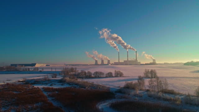 the bad ecology. the thermal power plant near by big city in the cold winter's day. aerial drone video with panoramic camera motion.. - centrale termoelettrica video stock e b–roll