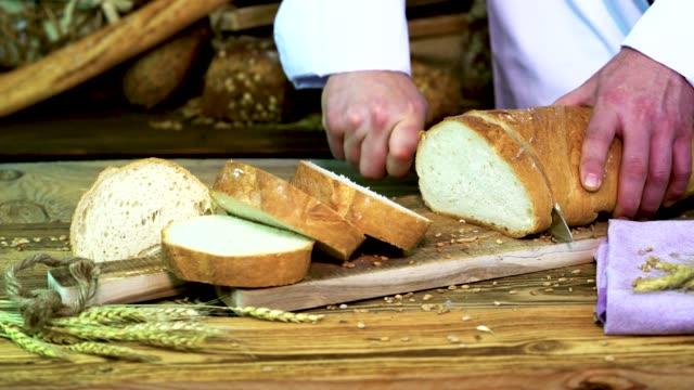 パン屋はテーブルの上に白いパンを切る。 - 食パン点の映像素材/bロール