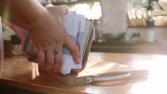 the baker pulls out the hot bread from the mold and puts it on the table - pane forno video stock e b–roll