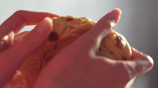 The baker slowly and beautifully breaks the finished dough close-up and rolls it out in his hands slowmo