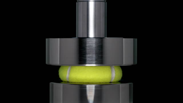 the ball from the big tennis presses hydraulic press, close-up - flessibilità video stock e b–roll
