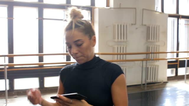 ballerinan praxis i stora hallen och lyssnar på musik på din smartphone - balettstång bildbanksvideor och videomaterial från bakom kulisserna