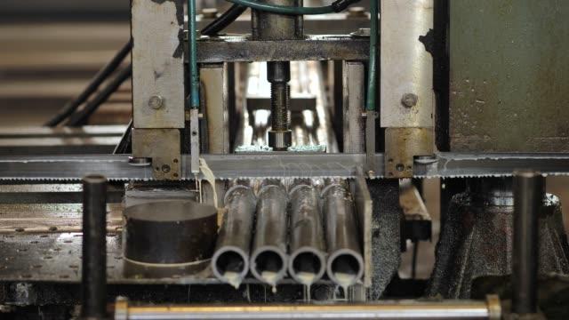 die bandsägemaschine schneidet rohe metallstangen mit der kühlflüssigkeit. die industrielle sägemaschine schneidet die materialstange. - bandsäge stock-videos und b-roll-filmmaterial