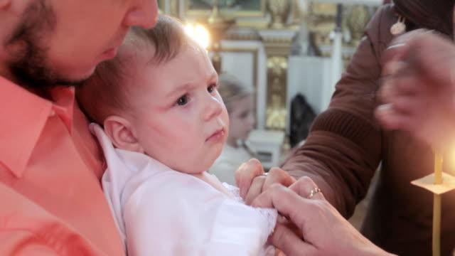 vidéos et rushes de le baptême de l'enfant dans l'église - baptême