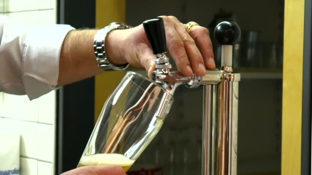 The barman pours beer in a glass video