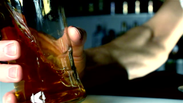 The barman's hand catches a bottle of alcohol in slow motion video