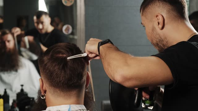 The barrier creates the client's hairstyle. In his hands he holds a mirror.